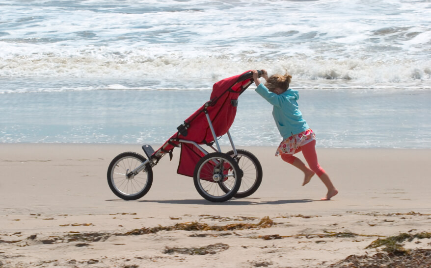A young girl perserveres in pushing a carriage along the beach in Santa Barbara, California.
